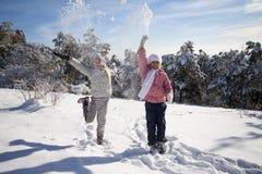Zwei Mädchen, die auf Schnee spielen stockfotos