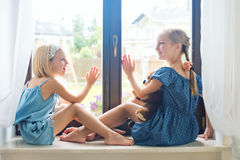 Zwei Mädchen, die auf Schwelle nahe Fenster am Privathaus sitzen Lizenzfreie Stockfotos