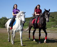 Zwei Mädchen, die auf zu Pferde gehen Stockbild