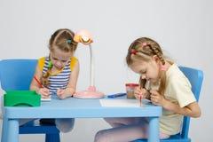 Zwei Mädchen, die bei Tisch Farben und Bleistifte des abgehobenen Betrages zeichnen Stockfoto