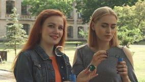 Zwei Mädchen, die draußen Blasen durchbrennen lizenzfreie stockfotografie