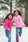 Zwei Mädchen, die durch den Schnee laufen Lizenzfreies Stockfoto