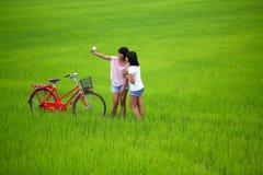 Zwei Mädchen, die ein Foto mit Fahrrad auf dem Paddygebiet nehmen Lizenzfreies Stockbild