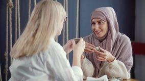 Zwei Mädchen, die ein reizendes Gespräch Innen über Tee haben stock video