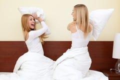 Zwei Mädchen, die eine Kissenschlacht im Schlafzimmer haben Lizenzfreie Stockfotografie
