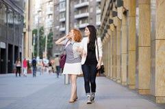 Zwei Mädchen, die in eine Stadt gehen lizenzfreie stockfotografie