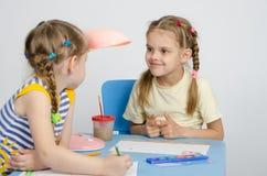 Zwei Mädchen, die eine Tabelle betrachtet einander zeichnen Lizenzfreie Stockfotos