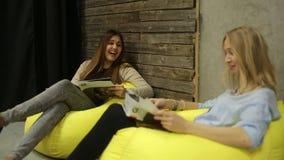 Zwei Mädchen, die eine Zeitschrift sitzen und lesen stock footage