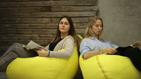 Zwei Mädchen, die eine Zeitschrift sprechen und lesen stock footage