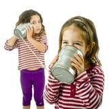 Zwei Mädchen, die an einem Zinntelefon sprechen Lizenzfreie Stockfotos