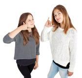 Zwei Mädchen, die einen Anruf mich machen Stockfotografie