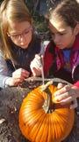 Zwei Mädchen, die einen Kürbis schnitzen Lizenzfreies Stockfoto