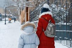 Zwei Mädchen, die entlang die schneebedeckte Straße des Winters der Stadt gehen, Kinder sind Händchenhalten, hintere Ansicht stockfotos