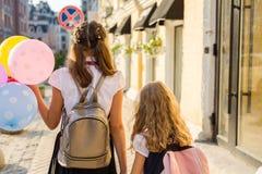 Zwei Mädchen, die entlang die Straße mit Ballonen gehen Lizenzfreie Stockfotografie