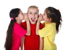 Zwei Mädchen, die etwas zum dritten Mädchen flüstern stockbild
