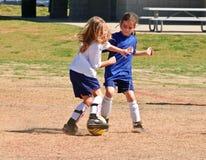 Zwei Mädchen, die für die Kugel/den Fußball kämpfen stockbilder