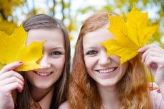 Zwei Mädchen, die Gesichter hinter Ahornblättern verstecken Lizenzfreie Stockfotos