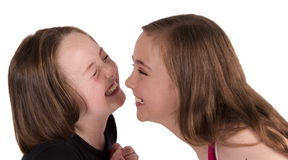 Zwei Mädchen, die Gesichter lachen und ziehen Lizenzfreies Stockfoto