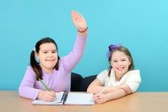 Zwei Mädchen, die ihre Schule tun, arbeiten im Klassenzimmer Stockbild