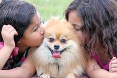Zwei Mädchen, die ihren Hund küssen Lizenzfreies Stockfoto