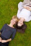 Zwei Mädchen, die im Gras liegen Lizenzfreies Stockbild
