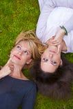 Zwei Mädchen, die im Gras liegen Lizenzfreie Stockbilder