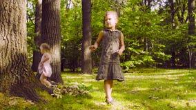Zwei Mädchen, die im Park auf dem Gras nahe dem Baum spielen stock video