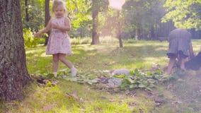 Zwei Mädchen, die im Park auf dem Gras nahe dem Baum spielen stock footage