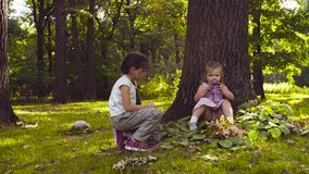 Zwei Mädchen, die im Park auf dem Gras unter den Bäumen spielen stock footage