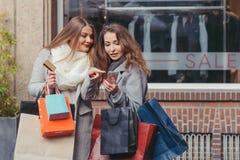 Zwei Mädchen, die intelligentes Telefon vor showwindow mit Salz betrachten Lizenzfreie Stockbilder