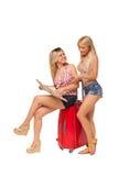 Zwei Mädchen, die kurze Jeanshose mit Karte und rotem Koffer tragen Stockfotografie