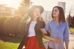 Zwei Mädchen, die mit dem Einkaufen auf Stadtstraßen gehen stockfotografie