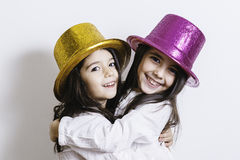Zwei Mädchen, die mit den gelben und rosa glänzenden Hüten aufwerfen Stockbilder