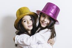 Zwei Mädchen, die mit den gelben und rosa glänzenden Hüten aufwerfen Stockfoto
