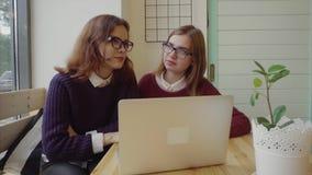 Zwei Mädchen, die mit Freunden über webchat sprechen oder einen Videochat im Café haben stock video footage