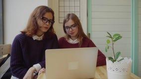 Zwei Mädchen, die mit Freunden über webchat sprechen oder einen Videochat im Café haben stock video