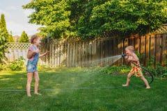 Zwei Mädchen, die mit Gartenarbeithaus auf Hinterhof am Sommertag sich spritzen lizenzfreie stockfotografie