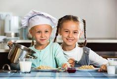 Zwei Mädchen, die mit Hafermehlbrei frühstücken lizenzfreie stockbilder