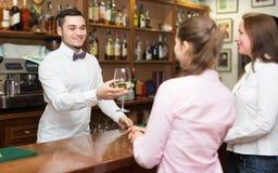 Zwei Mädchen, die mit Kellner flirten Lizenzfreies Stockfoto