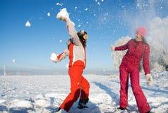 Zwei Mädchen, die mit Schnee spielen stockfotografie