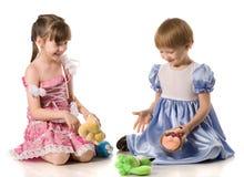 Zwei Mädchen, die mit Spielwaren auf dem Fußboden spielen Stockfotos
