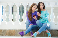 Zwei Mädchen, die Musik auf ihren Smartphones hören Lizenzfreie Stockbilder