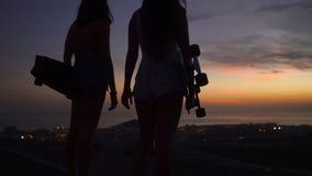 Zwei Mädchen, die am Rand der Straße mit Skateboards in ihren Händen aufpassen den Sonnenuntergang stehen stock video