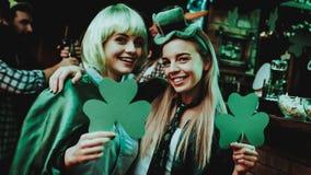 Zwei Mädchen, die a-Shamrocks halten St Patrick ` s Tag lizenzfreies stockbild