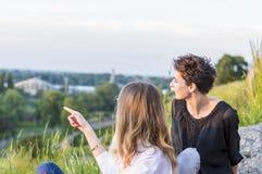 zwei Mädchen, die Sonnenuntergang genießen stockfoto