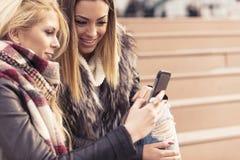 Zwei Mädchen, die Spaß beim Trinken des Kaffees haben Stockbild