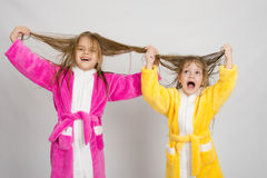 Zwei Mädchen, die Spaß in den Hausmänteln haben, halten nasses Haar lizenzfreies stockbild