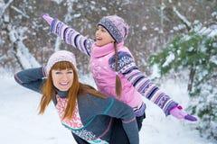 Zwei Mädchen, die Spaß im Winter haben lizenzfreie stockbilder