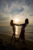 Zwei Mädchen, die Spaß am Strand haben Lizenzfreies Stockbild