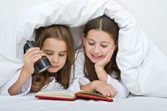 Zwei Mädchen, die unter Decke lesen Lizenzfreie Stockfotografie